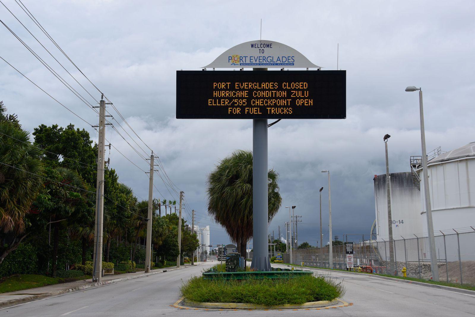 une grande et grande enseigne en métal du port des Everglades avec un fond noir et un lettrage lumineux orange se trouve au centre de l'image.  Ça lit,
