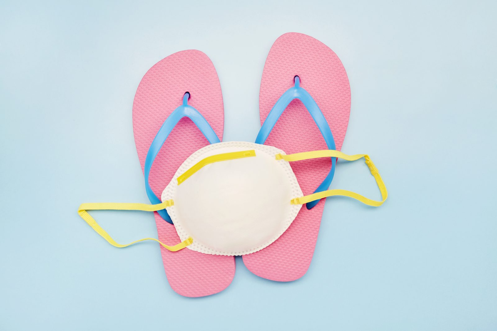 Still life of a white face mask and pink flip-flops on blue background, on vacation with a face mask