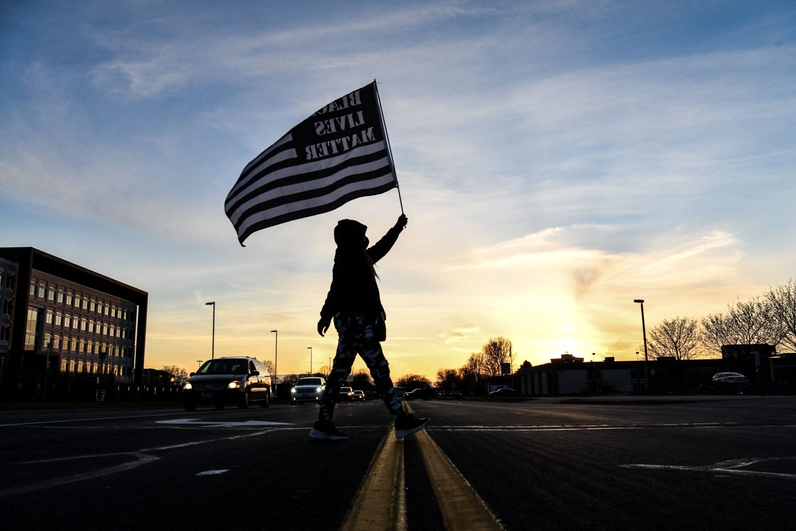 A demonstrator marches, holding a Black Lives Matter flag, during the sixth night of protests over the shooting death of Daunte Wright by a police officer in Brooklyn Center, Minnesota on April 16, 2021.