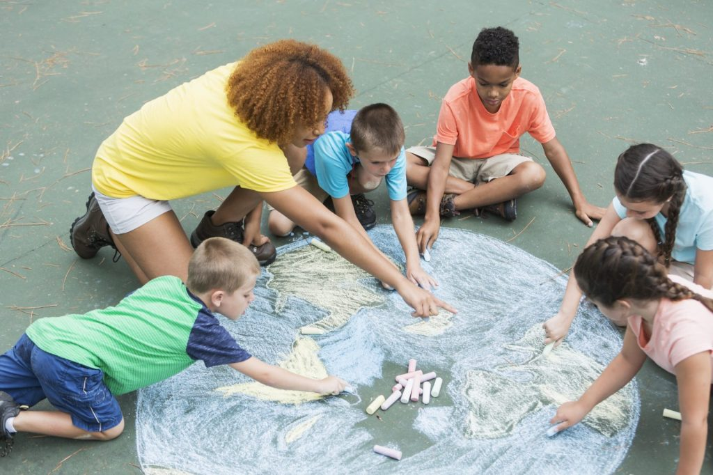 An educator helping young kids make a chalk drawing of the earth
