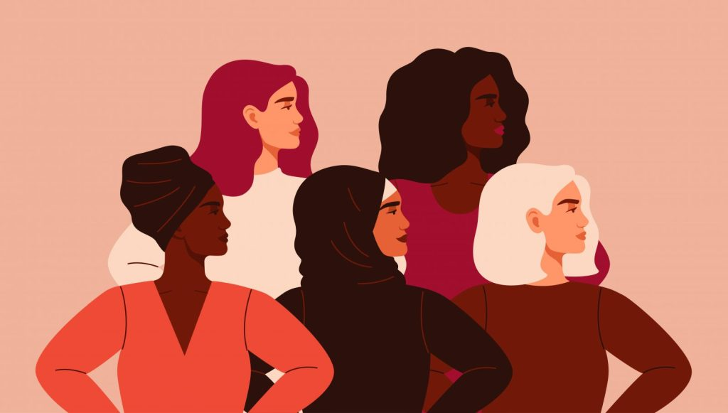 Five women of different nationalities and cultures standing together