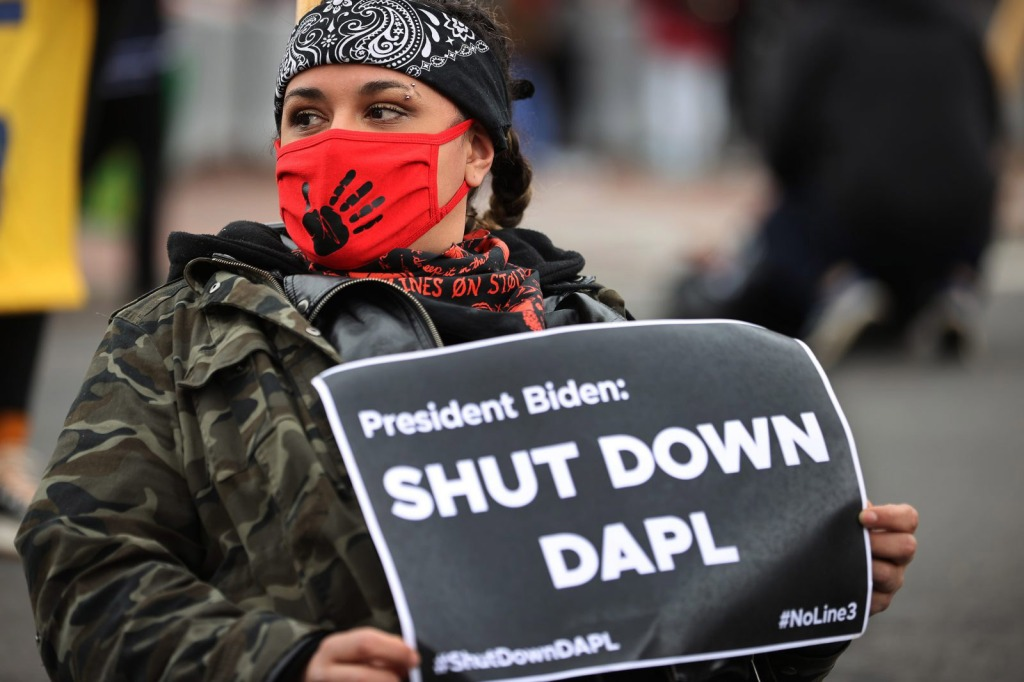 Woman holding a sign protesting the Dakota Access Pipeline