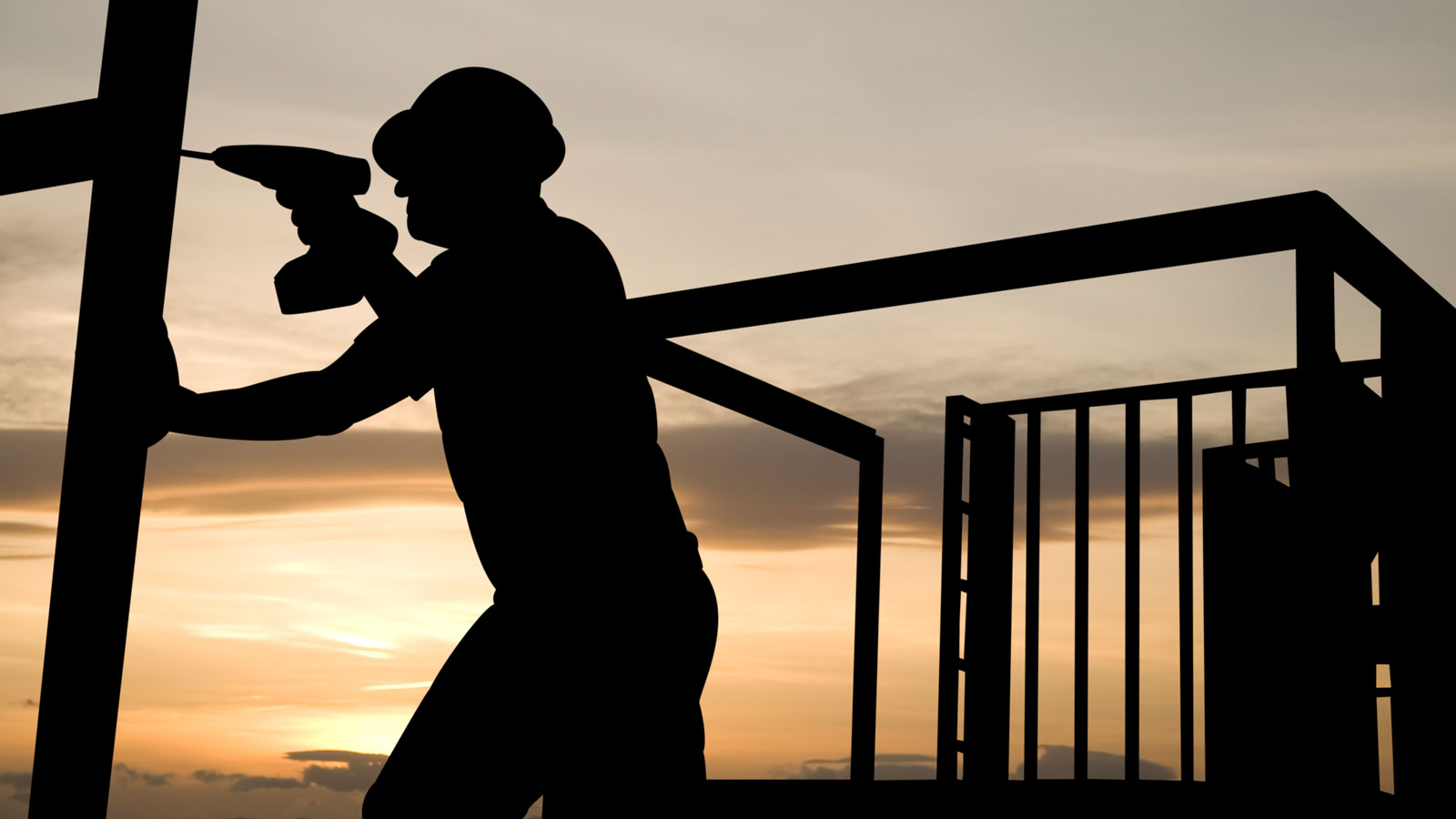 A construction worker uses a drill as he works on a building frame.