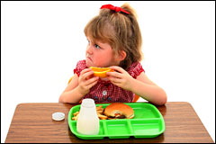 unhappy girl with school lunch tray