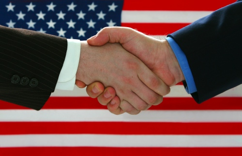 two hands shaking in front of an American flag.