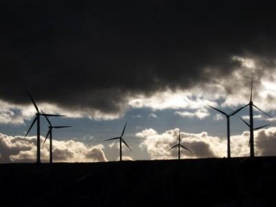 Wind turbines against dark clouds.