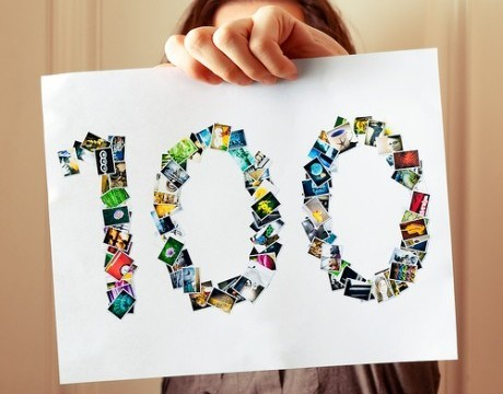 """hand holding """"100"""" sign"""