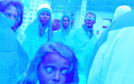 People on urban sidewalk, with blue tint.