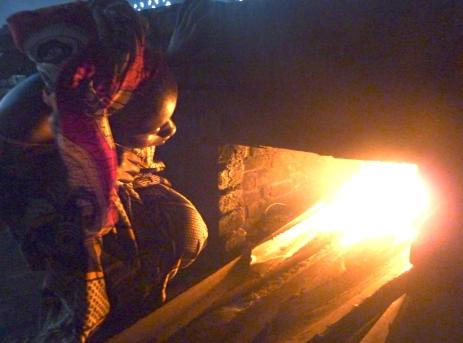 Woman tending fire.