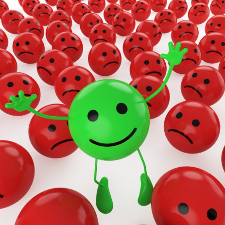 green smiley face amidst red frowny faces