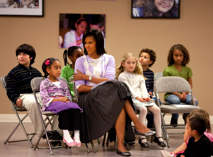 First Lady Michelle Obama sits with students during a visit to the LAMB bilingual school.
