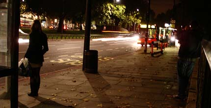 A lone woman waits at a bus stop.