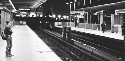 A lone woman waits at a transit stop.