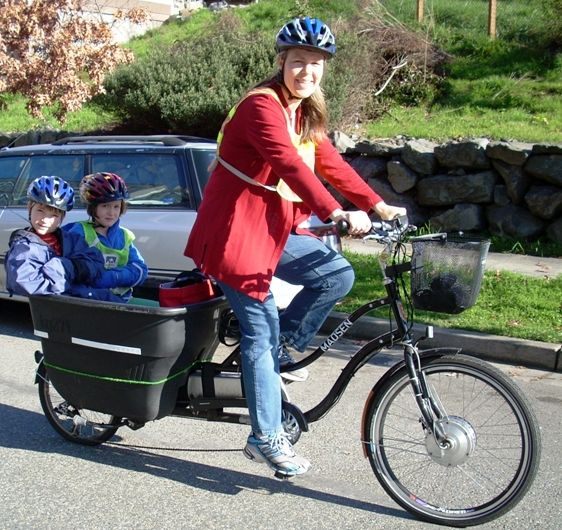 Lady on electric bike with children.