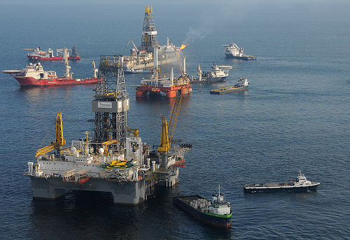 "A mobile offshore drilling unit (near), is prepared to drill a relief well at the Deepwater Horizon site. An additional MODU holds position directly over the damaged blowout preventer. While the drillship Discover Enterprise (far) continues to capture oil from the ruptured riser, preparations for the possible utilization of a ""junk shot"" or the ""top kill"" method to stop the sea-bottom oil gusher are being made."