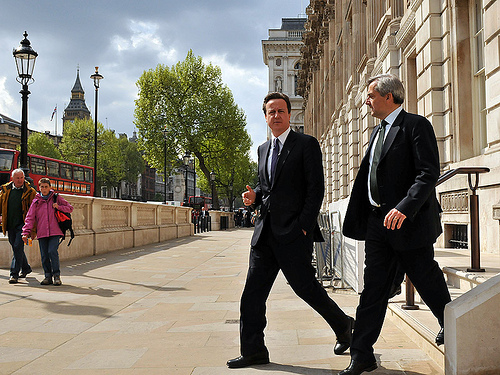 Prime Minister David Cameron and Energy and Climate Change Secretary Chris Huhne heading out to announce that the government will cut its greenhouse-gas emissions by 10 percent over the next 12 months.