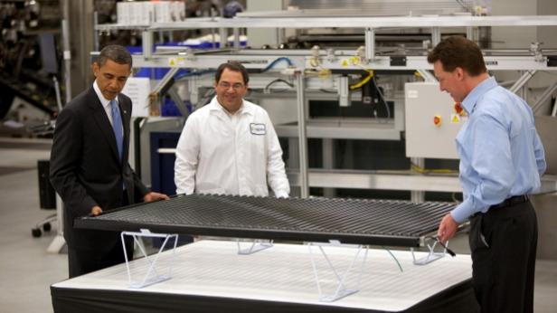 Obama examines a solar panel with Solyndra executives.