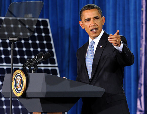 Obama speaking in front of a solar panel.