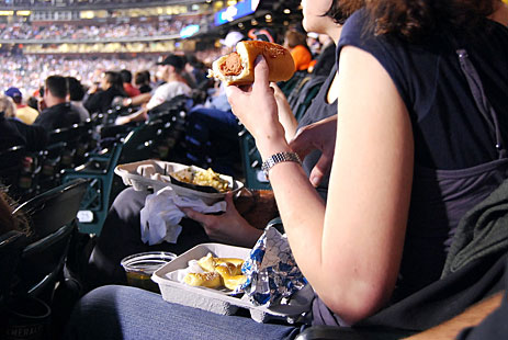 Woman eating hot dog at game