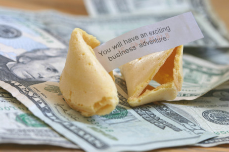 Fortune cookie on top of dollars.