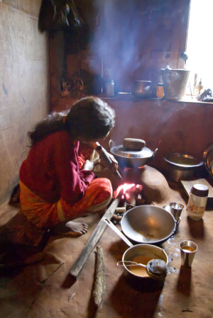 Woman cooking over wood stove.