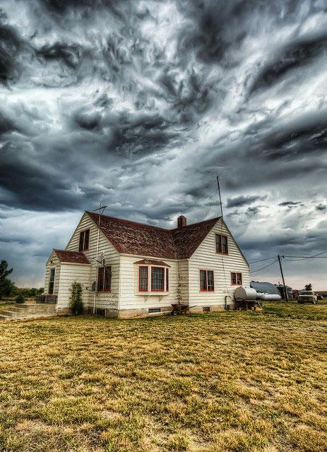 Tornado clouds over farmhouse