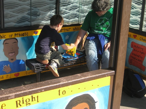 A man and his son play Connect 4 at a bus stop.