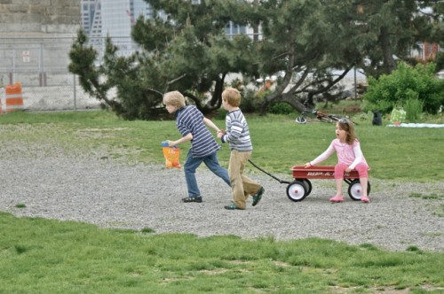 Kids with wagon in city park.