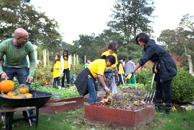 Michelle Obama and Sam Kass assist kids in the White House kitchen garden.