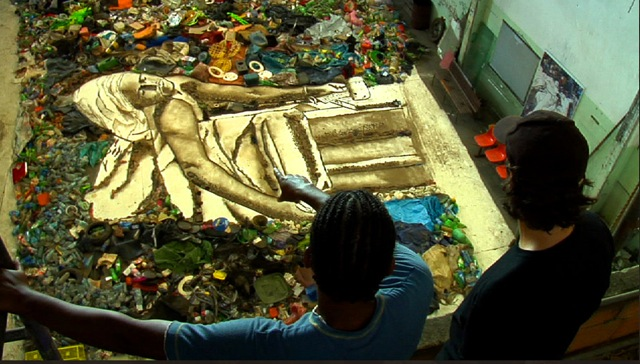 Artist looks at his work made of trash.