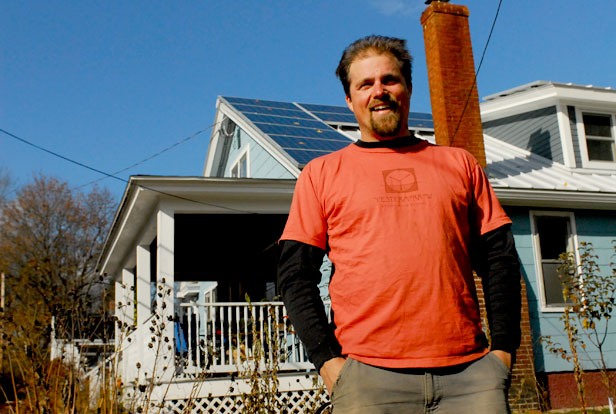 Chris Chaisson in front of a house with solar panels