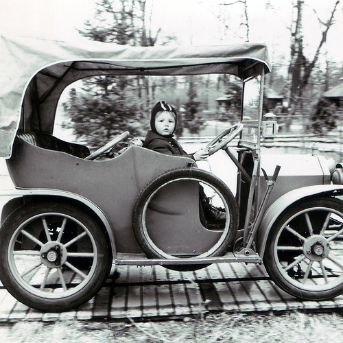 Kid in old car.