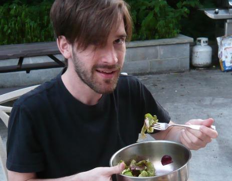 Man eating a salad, potentially a hegan.