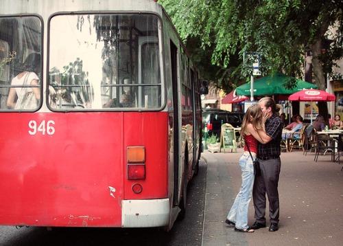 Couple kissing near a bus