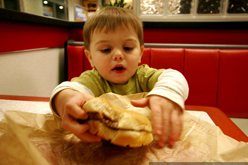 Kid with big burger.