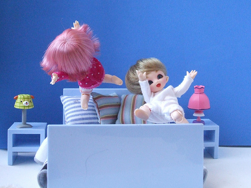 Dolls jumping on bed