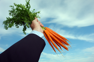 Business man holding carrots