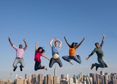 people jumping in front of city skyline