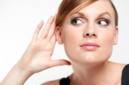 woman with hand cupped at ear