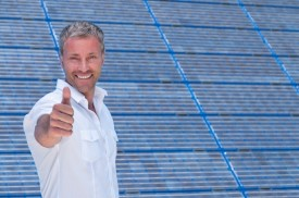man giving thumbs-up in front of solar panel