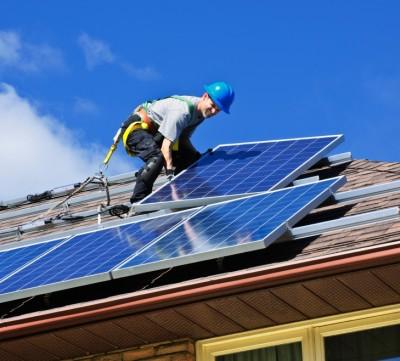 man on roof installing solar panels