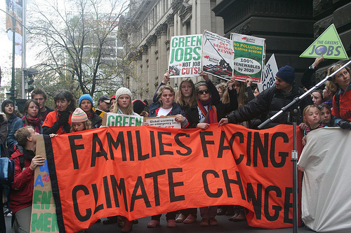 "protest with big sign: ""Families Facing Climate Change"""