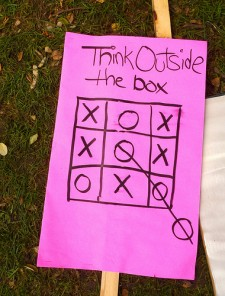 "protest sign: ""Think Outside the Box"""
