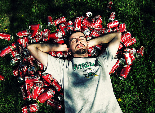Man surrounded by Coke cans.