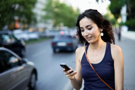 woman texting on sidewalk