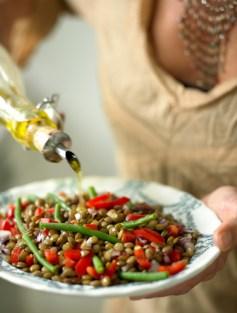 Woman dressing lentil salad.