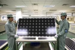 Chinese men holding solar panel