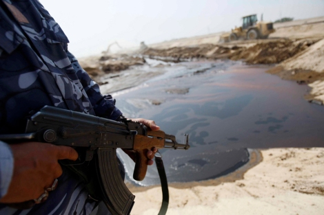 A policeman stands guard near a pool of oil that leaked from a damaged pipeline in Basra province.
