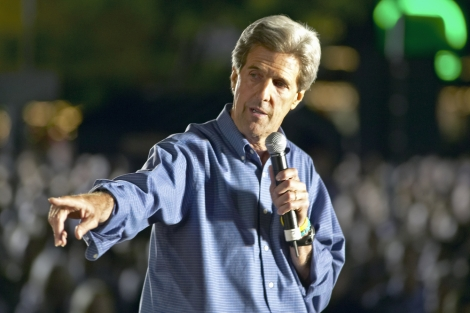 John Kerry points at a pile of stock