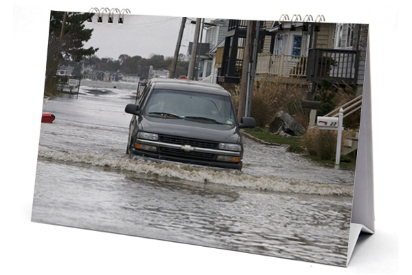 A vehicle makes its way through a flooded street of Milford, Connecticut